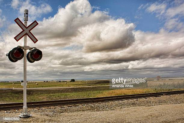 CONTENT] Landscape scene in rural Alberta with a railway crossing in the foreground flat prairie land stretches out for miles in the background a...