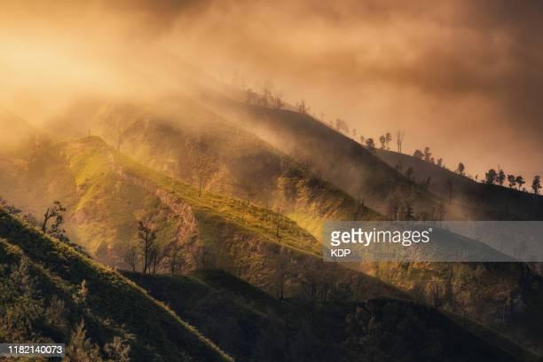 landscape scenery mountain range and sunlight natural phenomenon at kawah ijen crater national park, indonesia. - light natural phenomenon stock pictures, royalty-free photos & images