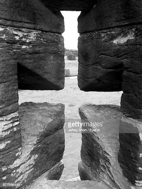 landscape seen through cross shape passage in rocks of alnwick castle - alnwick castle stock pictures, royalty-free photos & images
