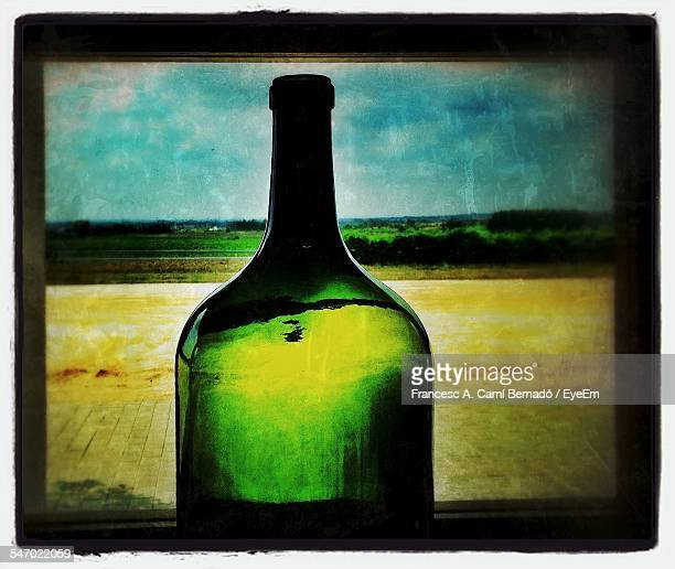 landscape seen through green bottle - bottle green stock pictures, royalty-free photos & images