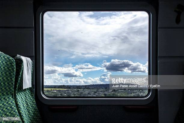 Landscape Seen Through Window Against Sky