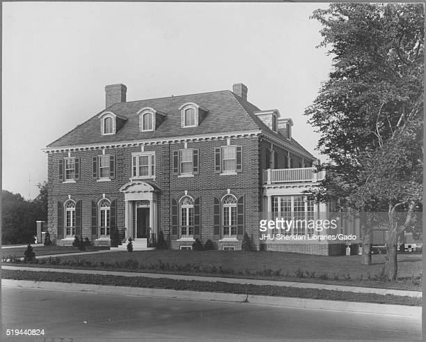 Landscape shot of a three-story brick house with a white entrance, white annexed sun room with a balcony on top, a chimney, with well-kept shrubbery...