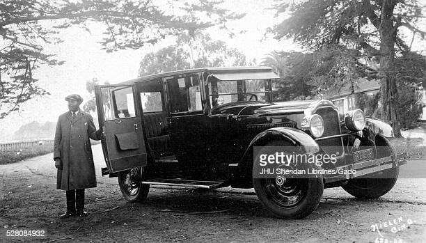 Landscape shot of Packard car, African American man holding the back door open wearing a hat and jacket, outdoors, 1920. .