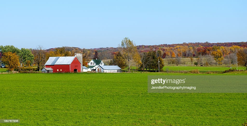 Landscape view of red Midwestern dairy farmhouse and land : Stock Photo