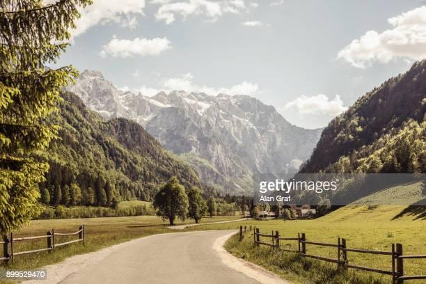 landscape view of rural road in valley and mountains, mozirje, brezovica, slovenia - valle foto e immagini stock