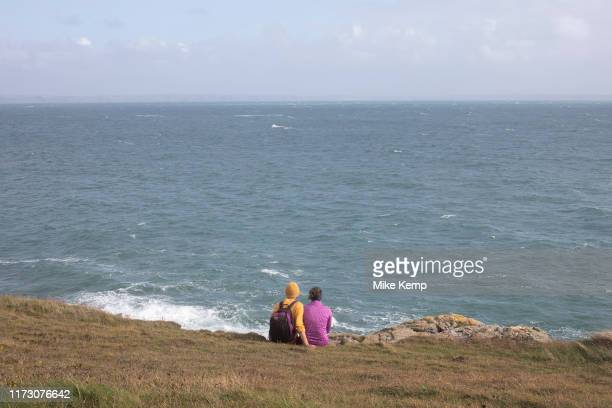Landscape view of two people looking out across rocks and headland out to sea at St Davids Head near St Davids Pembrokeshire Wales United Kingdom