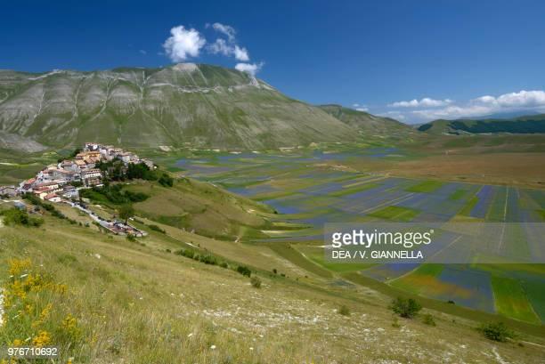 Landscape view over Pian Grande, Pian Piccolo, and Cima del Redentore with the village of Castelluccio di Norcia in the foreground, Monti Sibillini...