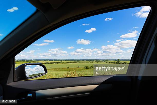 Landscape view through the window of a car with rearview mirror