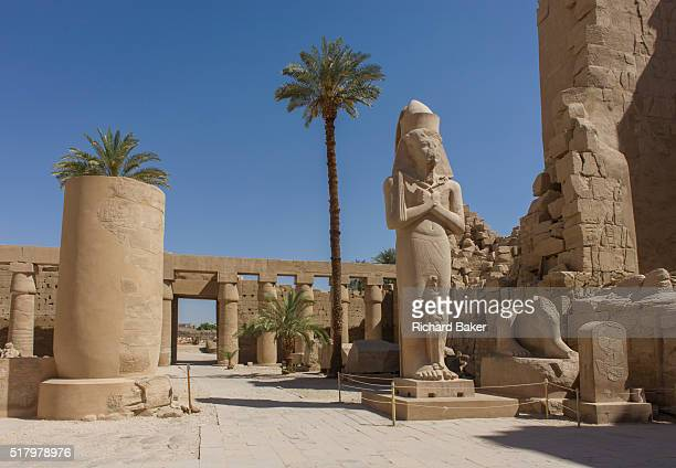 Landscape void of tourists showing the giant colossus of Pharaoh Ramesses ll and his daughter Bintanath at the ancient Egyptian Temple of Karnak,...