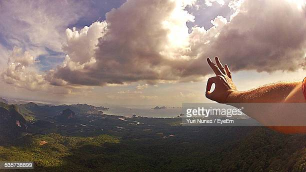 Landscape With Clouds And Human Hand Forming Ok Sign