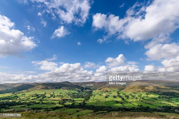 landscape with fields and distant mountains under a cloudy sky, peak district national park. - south yorkshire stock pictures, royalty-free photos & images