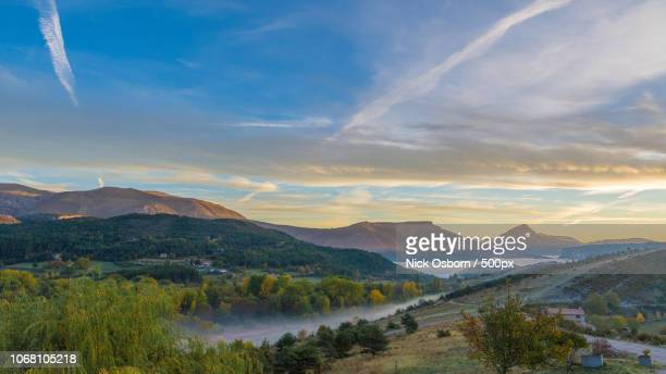 landscape with hills and buildings at sunrise - alpes de haute provence stockfoto's en -beelden