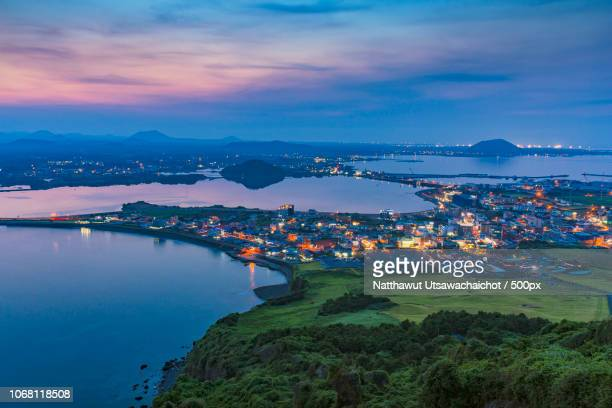 landscape with illuminated town at sunset from high angle view - jeju island stock pictures, royalty-free photos & images