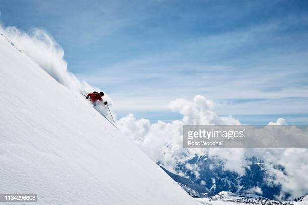 landscape with male skier skiing down steep mountainside, alpe-d'huez, rhone-alpes, france - alpine skiing stock pictures, royalty-free photos & images