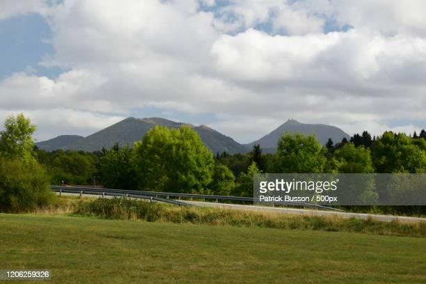 landscape with meadow, road, trees and puy de sancy mountain, ceyrat, auvergne-rhone-alpes, france - auvergne rhône alpes stock pictures, royalty-free photos & images