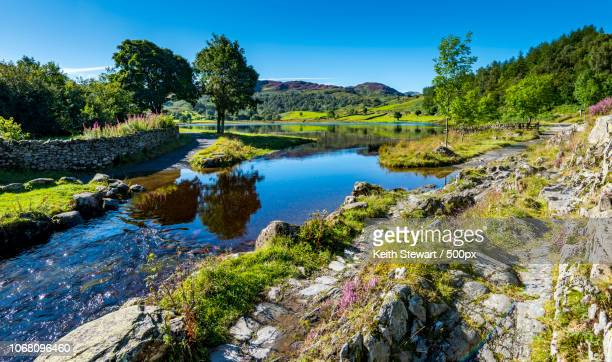 landscape with rock formations over lake - lake district stockfoto's en -beelden