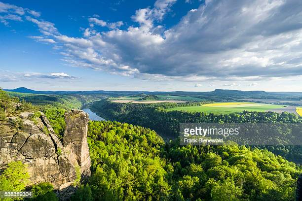 BAD SCHANDAU SAXONY GERMANY Landscape with rock formations rapeseed field trees and cloudy blue sky in the National Park Saxonian Switzerland the...