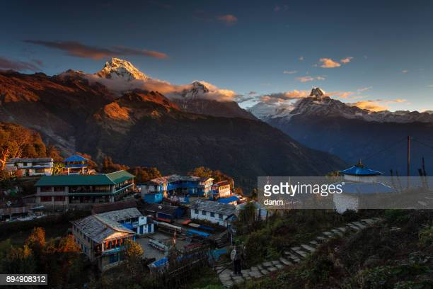 Landscape with Tadapani village on sunrise with Annapurna South, Hiunchuli and Machapuchare Fishtail Peaks in background. Himalaya Mountains, Nepal.