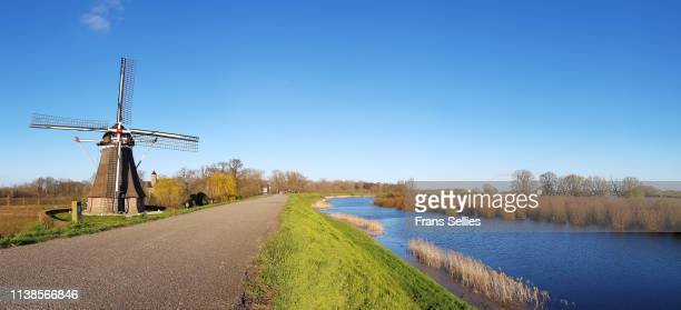 landscape with windmill, dyke and river foreland, the netherlands - gelderland stock pictures, royalty-free photos & images