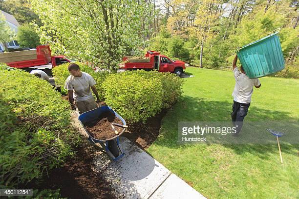 Paysagiste passer du paillis d'un camion et porter une mauvaise herbe bin