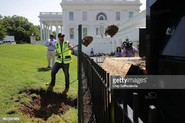 Landscapers work to repair a sinkhole that opened on the lawn outside the north side of the White House West Wing May 25 2018 in Washington DC The...