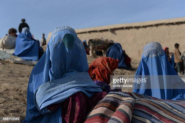 Landslideaffected Afghan villagers wait for donated supplies at the scene of the incident in Argo district in Badakhshan on May 4 2014 Rescue teams...