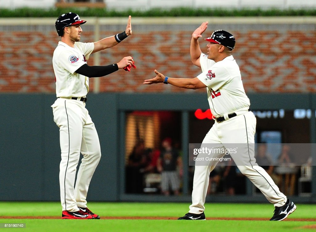 Lane Adams #16 of the Atlanta Braves is congratulated by First Base Coach Eddie Perez #12 after knocking in three runs with a pinch-hit sixth inning double against the Arizona Diamondbacks at SunTrust Park on July 15, 2017 in Atlanta, Georgia.