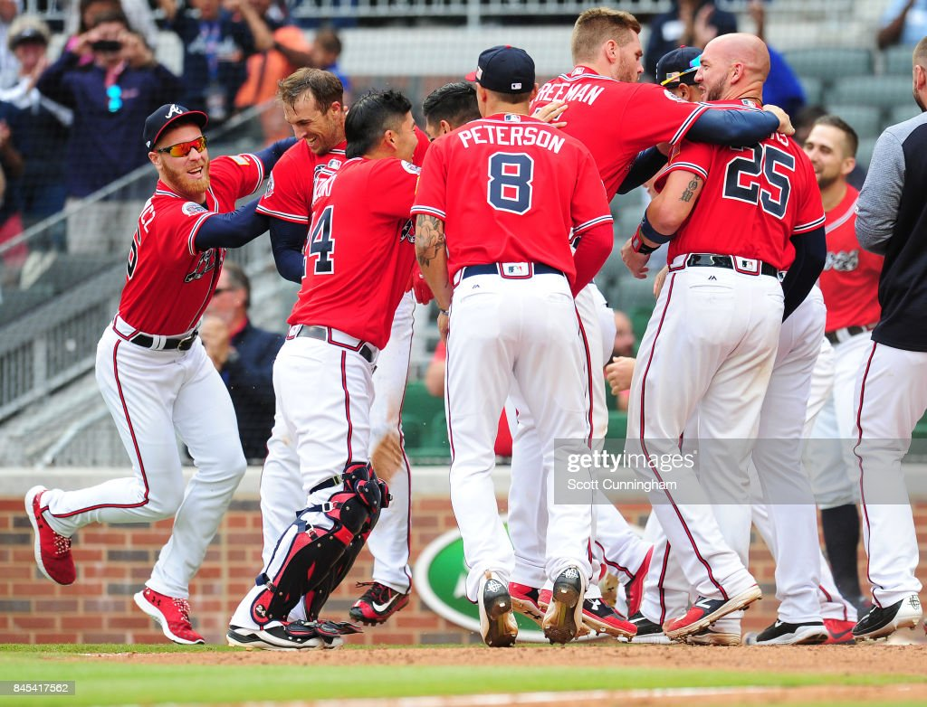 Lane Adams #16 of the Atlanta Braves (second from left) is congratulated by teammates after hitting a 10th inning two-run walkoff home run against the Miami Marlins at SunTrust Park on September 10, 2017 in Atlanta, Georgia.