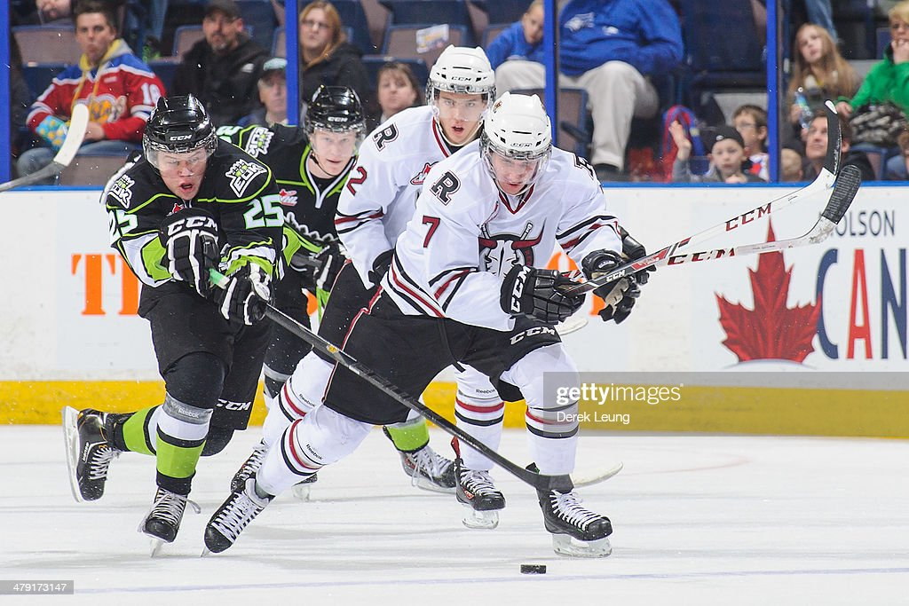 Lane Bauer #25 of the Edmonton Oil Kings tries to check Brady Gaudet #7 of the Red Deer Rebels during a WHL game at Rexall Place on March 16, 2014 in Edmonton, Alberta, Canada.
