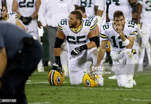 Lane Taylor and Aaron Rodgers of the Green Bay Packers kneel while Davante Adams is attended to after being injured in the third quarter against the...