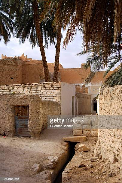 lane with a pile of mud bricks in the backyards of the oasis of ghadames, unesco world heritage, libya - れんが造りの家 ストックフォトと画像
