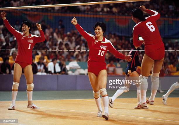 Lang Ping, Yang Xiaojun and Yang Xilan of the China women's volleyball team celebrate their gold medal 3 - 0 win over the United States in the final...