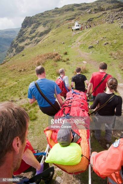 Langdale/Ambleside Mountain Rescue Team carrying an injured hiker to a helicopter