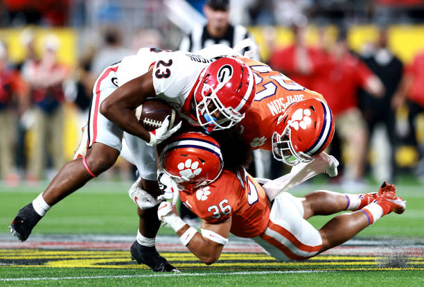 Lannden Zanders and Trenton Simpson of the Clemson Tigers tackle Jaylen Johnson of the Georgia Bulldogs during the second half of the Duke's Mayo...