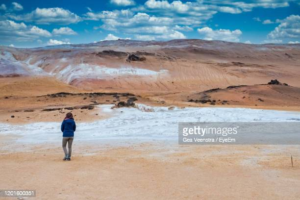 lanscape, girl is walking to a hill, horizontaal, in blue, white and brown colors. - horizontaal stock pictures, royalty-free photos & images