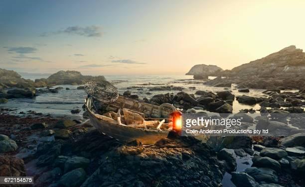 Lantern glowing on rowboat at rocky shore
