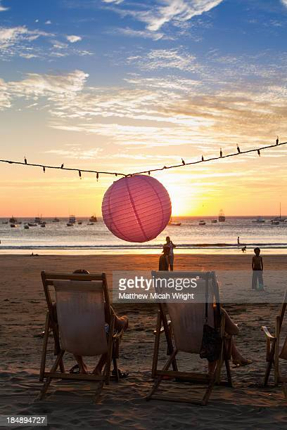 A lantern hangs over the beachfront at sunset