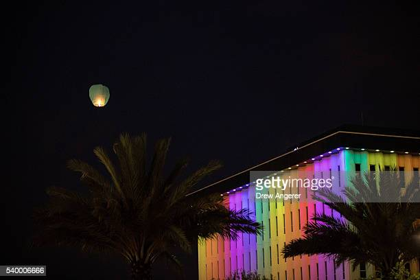 A lantern is released and flies over a hotel lit in rainbow colors after an evening memorial service for the victims of the Pulse Nightclub shootings...
