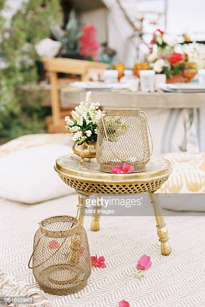 Lanterns and flowers on a small brass table outside a tent