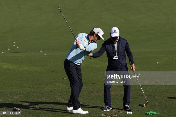 Lanto Griffin of the United States works with coach Todd Anderson on the range during a practice round prior to the Masters at Augusta National Golf...