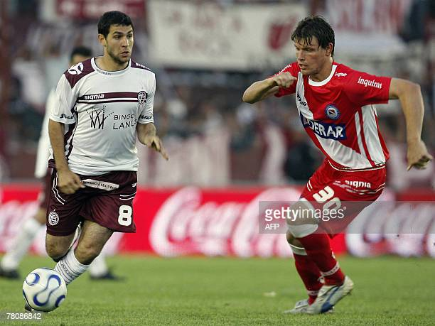 Lanus' Diego Valeri is marked by Roberto Battion of Argentinos Juniors during their Argentina first division football match in Buenos Aires 25...