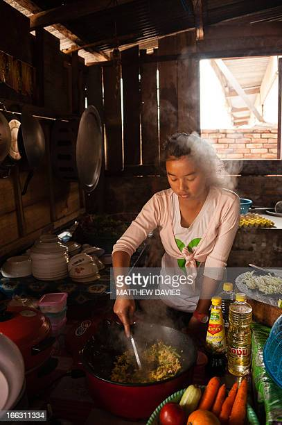Lao girl Cooks A Meal Of Fried Rice In A Rustic Kitchen In Boun Neua, Northern Laos.