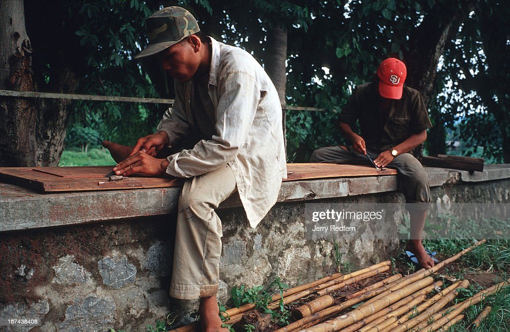 Lao laborers work on refinishing old shutters that will be...