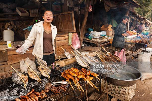 Lao Lady Cooking grilled fish And Chicken At Her Rustic Outdoor Stall Near Luang Prabang Laos