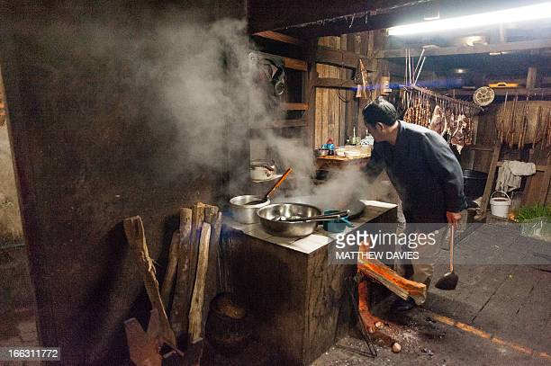 Lao Man Cooks In A Rustic Smoky Kitchen Using A Wood Fired Wok In The Lao Town, Phongsali. Laos