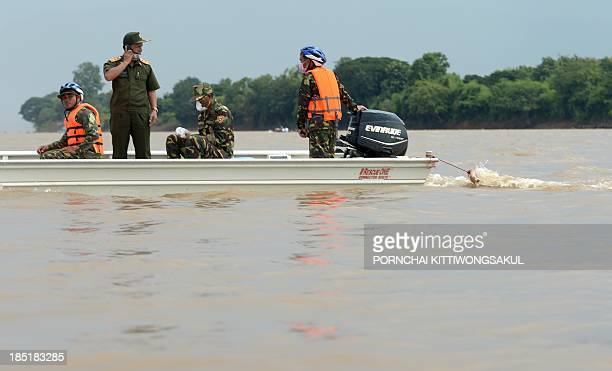 Lao soldiers search for bodies of passengers who died in the Lao Airlines plane crash from the waters of the Mekong river in Pakse town on October 18...