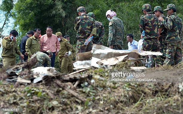 Lao soldiers stand next to pieces from a Lao Airlines plane after it crashed into the Mekong river near Pakse town on October 17 2013 Rescuers...