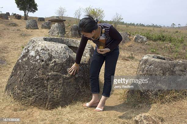 Lao tourist from the capital Vientiane tours Site 1 of the Plain of Jars near Phonsavan The jar she examines has a human figure carved on its side