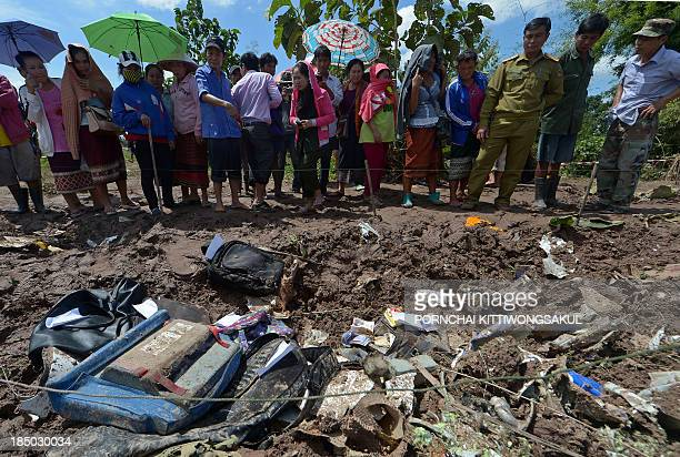 Lao villagers look at pieces of luggage from a Lao Airlines plane after it crashed into the Mekong river near Pakse town on October 17 2013 Rescuers...