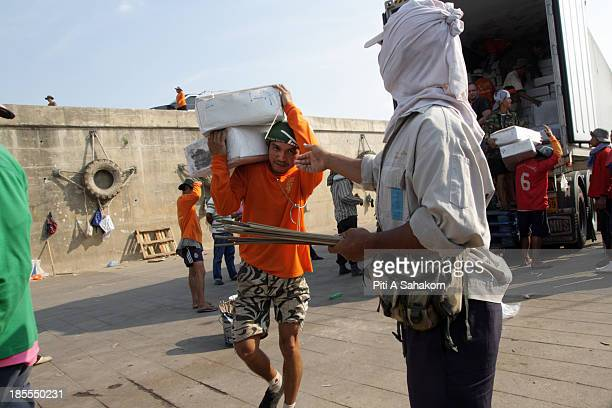 Lao workers carry goods from boats docked at Chiang Saen Commercial Port An important gateway in northern Thailand to the Greater Mekong Subregion...